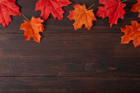 Autumn maple leaves on brown wooden table. Fall background with empty space for text. Top view Standard-Bild