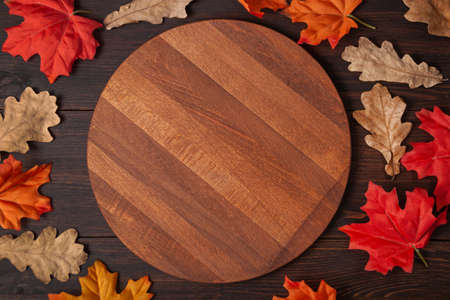 Round cutting board with autumn maple, oak leaves on brown wooden table. Backgroud for restaurant menu. Top view