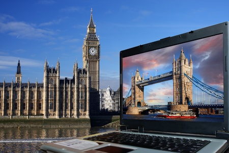 palace of westminster: Big Ben with Tower Bridge on screen of notebook, London, UK