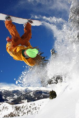 dropping: Snowboarders jumping against blue sky