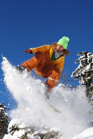 Snowboarders jumping against blue sky Stock Photo - 12021049