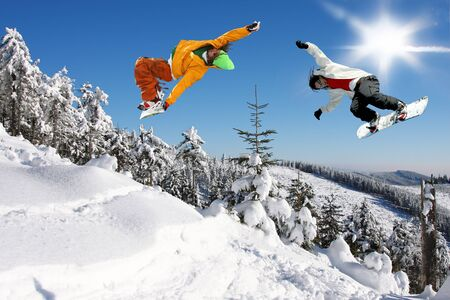 snow drop: Snowboarders jumping against blue sky
