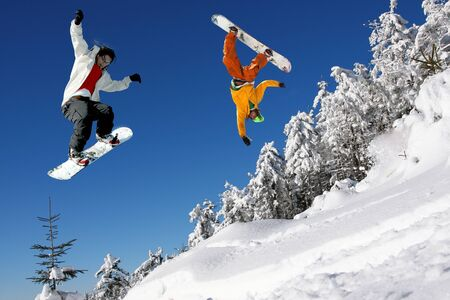 snowboarder jumping: Snowboarders jumping against blue sky