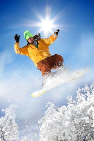 スノーボーダーの青い空を背景にジャンプ