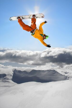 dropping: Snowboarder jumping against blue sky  Stock Photo