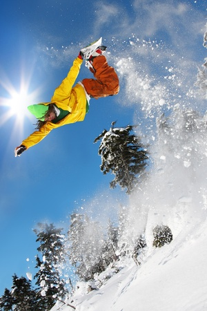 Snowboarder jumping against blue sky photo