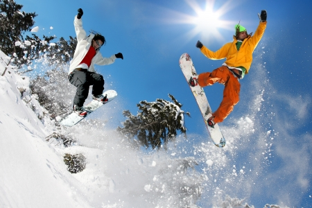 Snowboardisté skákání proti modré obloze