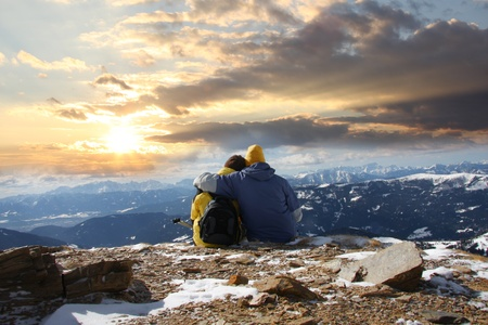 chearful: Young happy couple in snowy mountains against sunset  Stock Photo