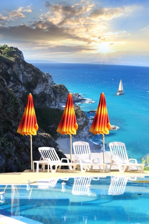 resorts: Luxury swimming pool with azure sea  Stock Photo