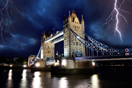 british weather: Tower Bridge with lightnings at stormy night in London, UK