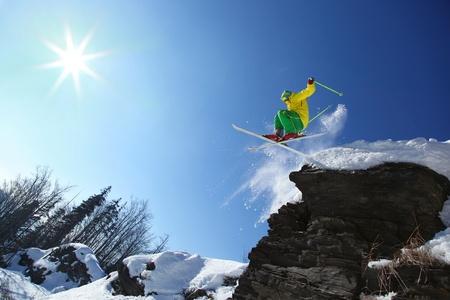 skieer: Skiër springen tegen blauwe hemel van de rots