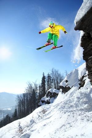 ski slopes: Sciatore saltando contro il cielo blu dalla roccia