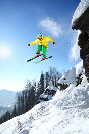 downhill: Skier jumping against blue sky from the rock