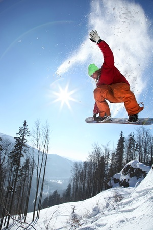 Snowboarder jumping against blue sky Stock Photo