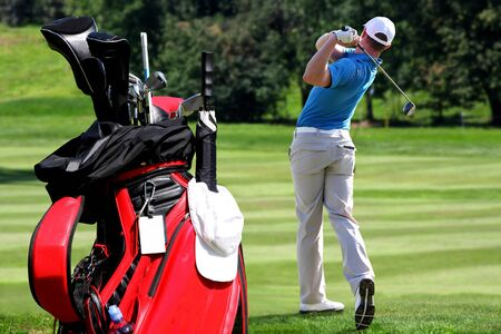 Man playing golf with golf bag