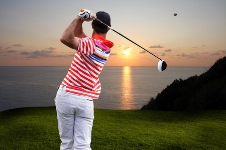 Man playing golf against sunset over sea photo