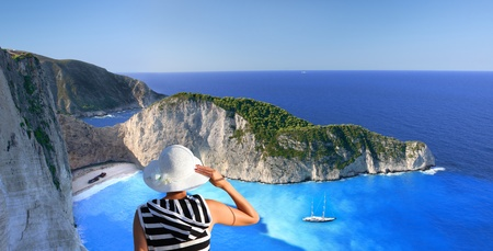 Navagio beach with woman on cliff, Zakynthos Island, Greece  photo