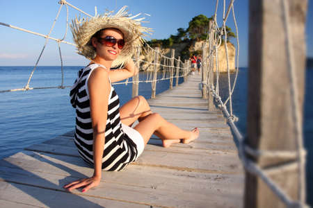 young woman sitting: Sexy Woman in summer Paradise on wooden bridge above sea Stock Photo