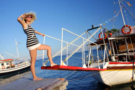 Happy Woman in marina with old boat photo