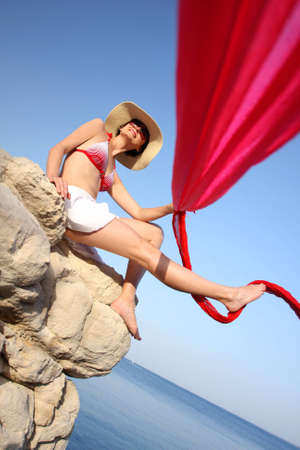 Sexy Woman sitting on the rock with red scarf above sea photo