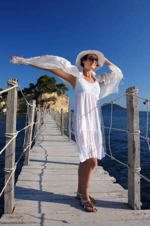 Sexy Woman on wooden bridge above sea photo