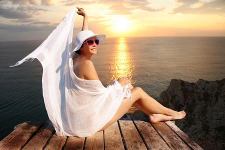 Sexy Woman with white scarf gainst sunset above sea photo