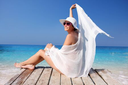 Sexy Woman with white scarf gainst azure sea photo
