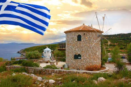 ionian island: Traditional Wind Mills with flag of   Greece Stock Photo