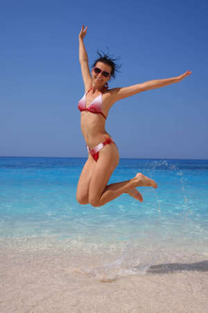 Happy Girl jumping on the beach  photo