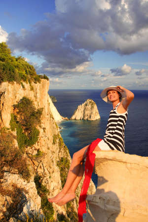 Sexy Woman on the rock above azure sea, Greece, Zakynthos Island  photo