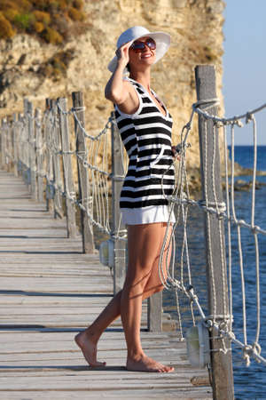 Sexy Woman in summer Paradise on wooden bridge above sea photo