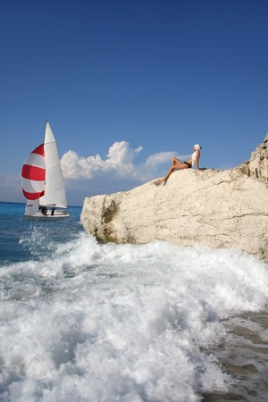 Sexy woman on the rock against yacht Stock Photo - 13059244