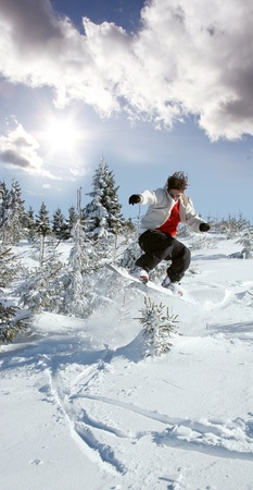 Snowboarder jumping against blue sky and sun rays photo