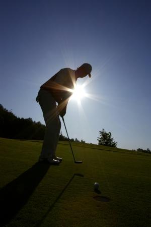 fairway: Man playing golf against sunset