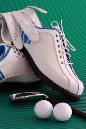 Golf shoes with glove, club and balls on green background photo