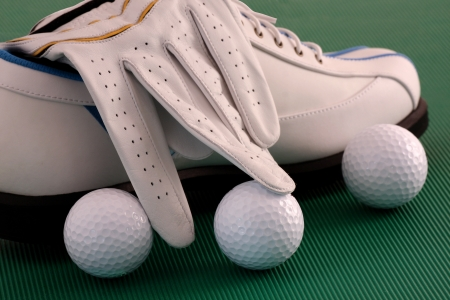 Golf shoes with glove,  and balls on green background photo