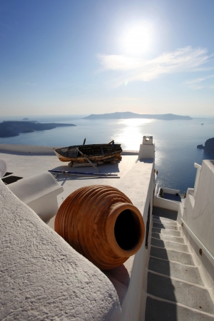 santorini caldera: Santorini with old Vase and boat on white roof in Fira, Greece Stock Photo
