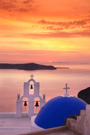 santorini: Santorini with Firostefani Church against sunset over sea, Fira, Greece Stock Photo