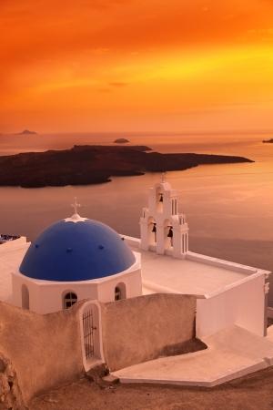Santorini with Firostefani Church against sunset over sea, Fira, Greece photo