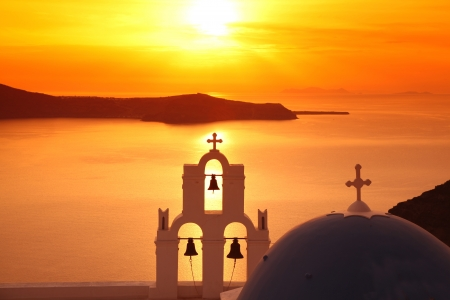 Santorini with Firostefani Church against sunset over sea, Fira, Greece Stock Photo