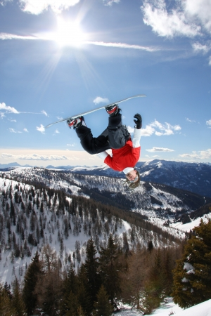 extreme: Snowboarder jumping against blue sky Stock Photo