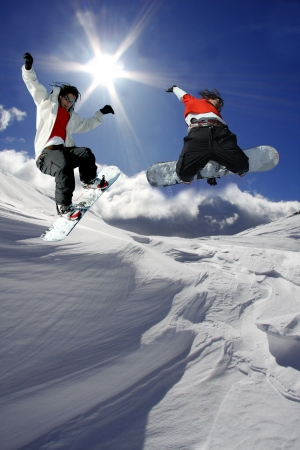 Snowboarders jumping against blue sky  Stock Photo - 14844500