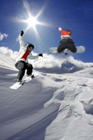 Snowboarders jumping against blue sky Stock Photo - 14844501