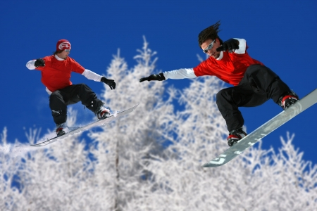 Snowboarders jumping against blue sky Stock Photo - 14844495