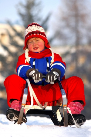 little girl during sledding at winter time photo