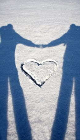 copys pace: shadow of lovers with heart on snow Stock Photo