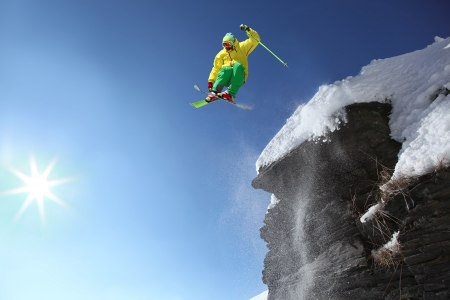Skier jumping though the air from the cliff in high mountains photo