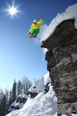 cliff jumping: Skier jumping though the air from the cliff in high mountains