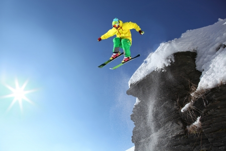 jump suit: Skier jumping though the air from the cliff in high mountains