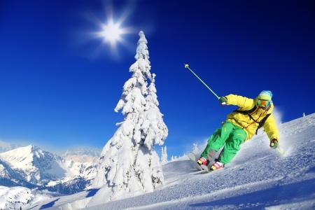 Skiër skiën afdaling in het hooggebergte